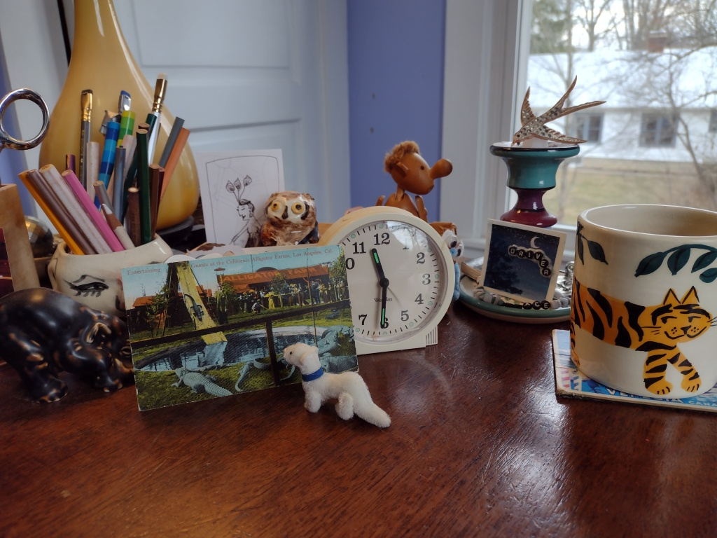 assemblage of small items on desk, ermine, elephant, mug with tiger on it, Hans Bolling figure, clock, pencils, etc.